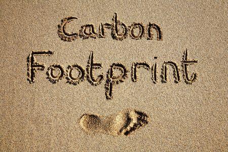 footprint: Huella del carb�n escrita en arena en una playa.