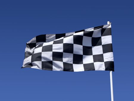 A checkered flag blowing in the wind at the end of a motor race. Stock Photo - 3177145