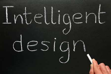 A teacher writing Intelligent Design on a blackboard. Stock Photo - 3415362