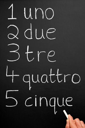 four classes: A teacher writing numbers one to five in the Italian language. Stock Photo