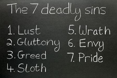Les sept péchés capitaux, écrit à la craie sur un tableau noir.