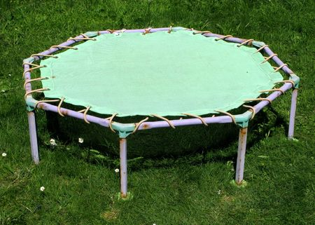 Close up of an old childrens trampoline on a garden lawn.