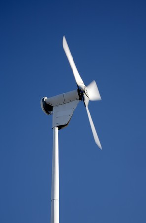 Small electricity generating wind turbine spinning with motion blur movement. photo