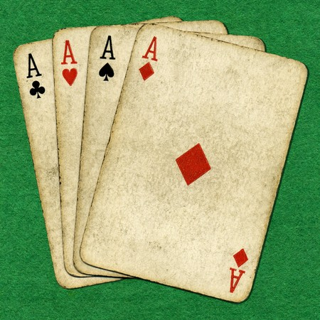 Four old vintage dirty aces poker cards on a green cloth. Stock Photo - 4164984