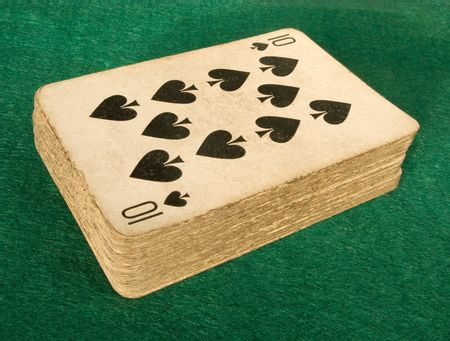 Old deck of cards on a green baize poker table. Stock Photo - 4225209