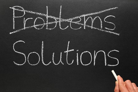 Crossing out problems and writing solutions on a blackboard. Stock Photo