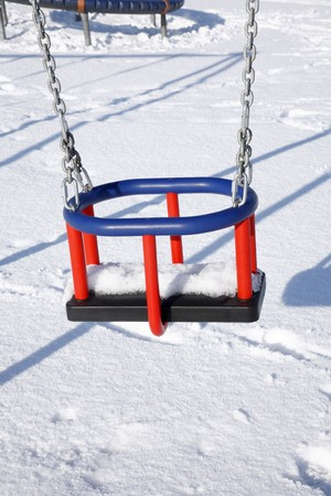 Empty childs swing in a park covered in snow. photo