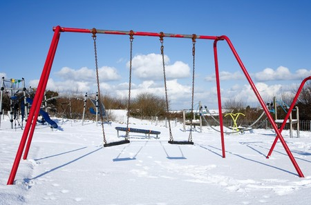 Childs swings in an empty park playground covered in snow. photo