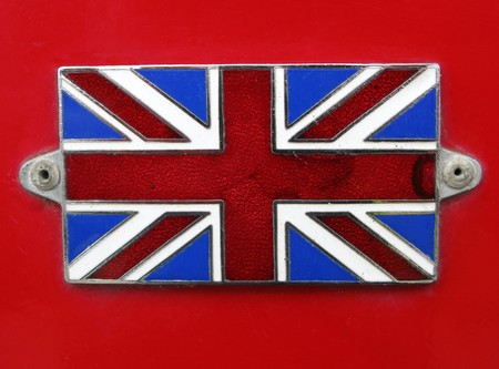 Vintage British Union Jack Flag badge on a red bus close up. photo