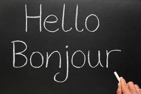 Bonjour, hello in French written on a blackboard.