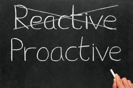 reactive: Crossing out reactive and writing proactive on a blackboard.