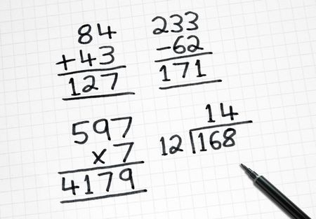 sums: Writing simple maths sums on square paper.