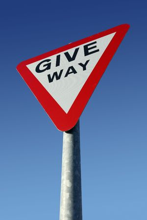 British give way road sign and a blue sky. photo