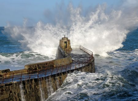 Big wave splash on Portreath pier, Cornwall UK. Stock Photo