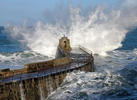 Big wave splash on Portreath pier, Cornwall UK. Stock Photo