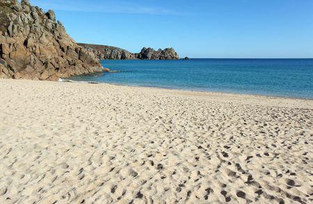 porthcurno: Porthcurno sandy beach and Logan rock in Cornwall UK. Stock Photo