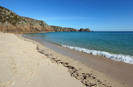porthcurno: Porthcurno sandy beach shore line and Logan rock in Cornwall UK.