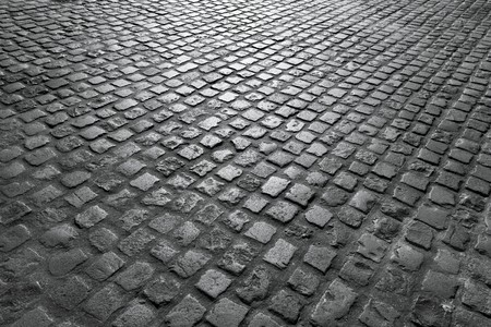 cobbled: Old English cobblestone road close up in black and white. Stock Photo