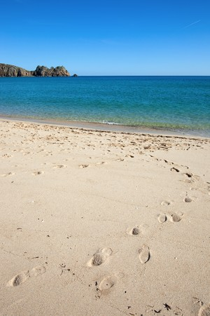 cornwall: Porthcurno sandy beach and Logan rock in Cornwall UK. Stock Photo