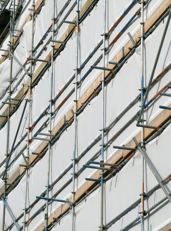 Close up building covered by scaffolding and white tarpaulin. photo
