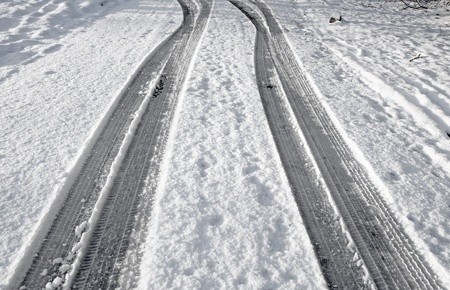road marks: Close up tyre tracks in snow on a road. Stock Photo