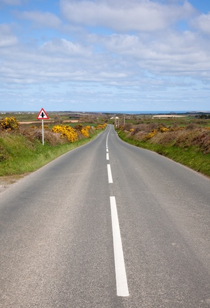 english countryside: English country road with the sea on the horizon.