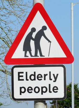 crossing: British elderly people crossing road warning sign.