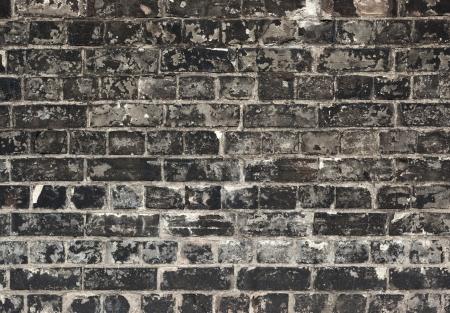Old weathered black brick wall texture close up. photo