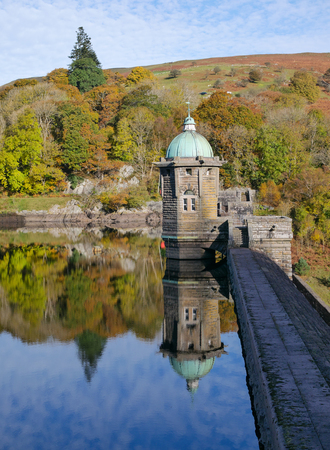 elan: Pen Y Garreg reservoir dam autumn tree colours reflections. Stock Photo