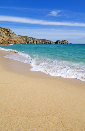 Porthcurno sandy beach shore and Logan rock in Cornwall England.