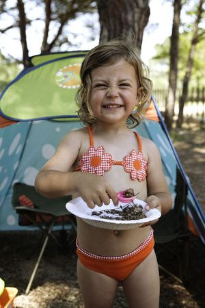 A young girl on a camping holiday holding a plate full of pine needles photo