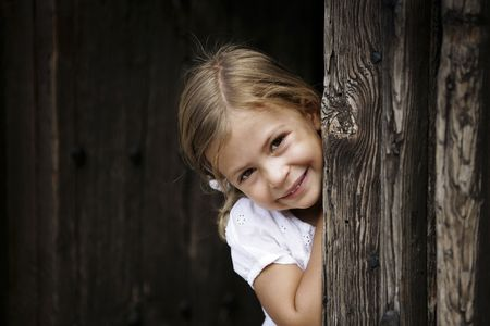 4 years old: Young girl leaning against door frame