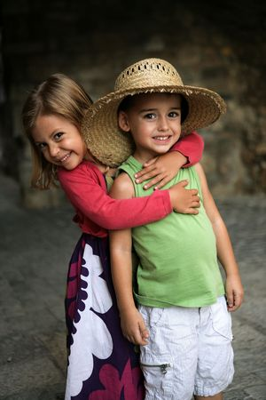A young girl puts her arm around her friend and gives him a hug photo