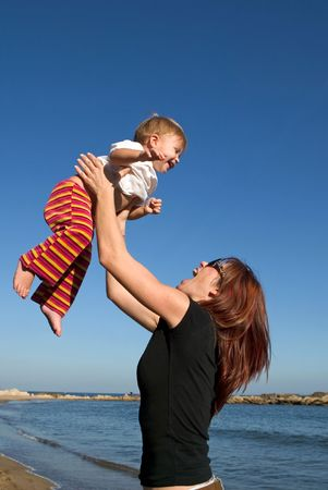 A mother lifts her child up into the air whilst on a beach  photo