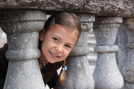 A young girl playing peek a boo through a gap in some columns Stock Photo - 6713284