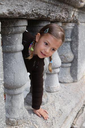 peek a boo: A young girl playing peek a boo through a gap in some columns