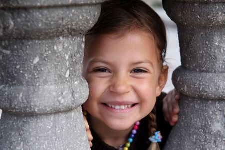 A young girl playing peek a boo through a gap in some columns Stock Photo - 6713286