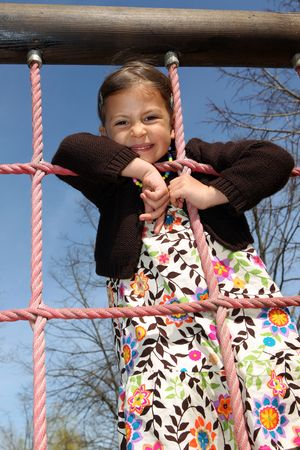 Young girl enjoys climbing up a rope ladder in a childrens playground photo