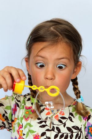 awe: Studio portrait of girl looking in awe at the huge bubble she has blown Stock Photo