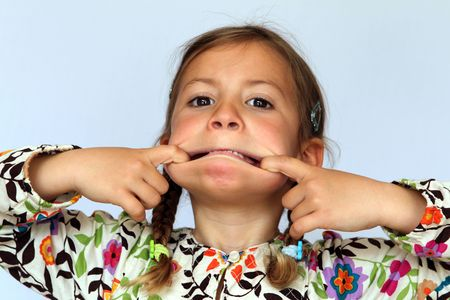 contorted: Studio portrait of young girl pulling a silly contorted face Stock Photo