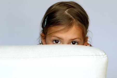 Shy young girl hiding behind the sofa photo