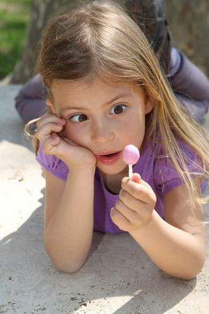 awe: Cute young girl looking in awe at a lollipop Stock Photo