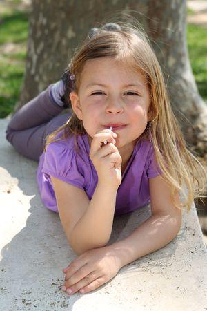 sucking lollipop: Cute young girl enjoys sucking a lollipop