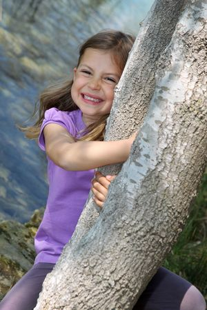 Cute young girl swinging from a tree trunk by a lake photo