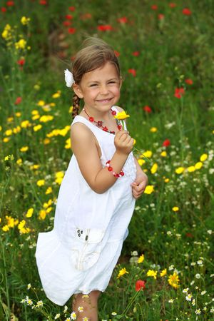 Pretty young girl holding a daisy flower that she has picked from a meadow photo