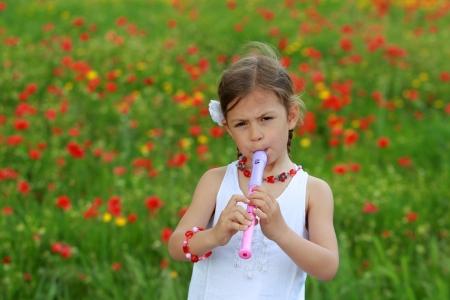 dwarsfluit: Vrij jong meisje spelen de recorder naast een papaver veld