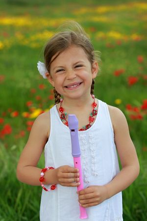 Pretty young girl posing with her musical recorder next to a poppy and daisy meadow photo