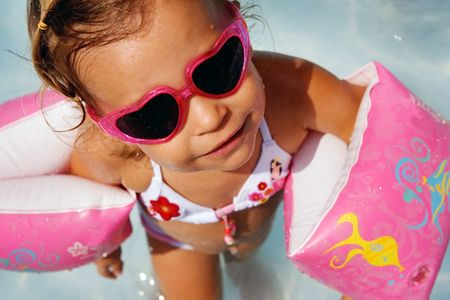 Little girl playing in a paddling pool and wearing armbands photo