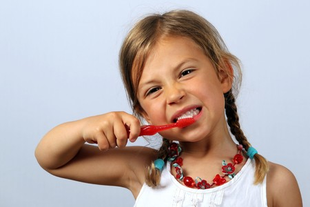 vigorously: Liitle girl brushing her teeth vigorously with a red toothbrush