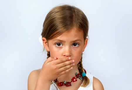 solemn: Little girl with hand over her mouth